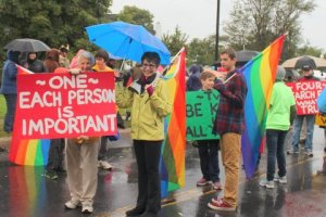 Picture of people holding rainbow flags and a sign that says each person is important