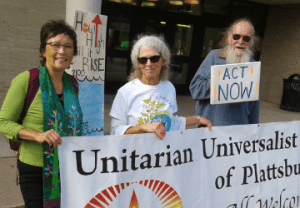 """Picture of members and minister at Earth Day rally holding banner and sign saying """"act now."""""""