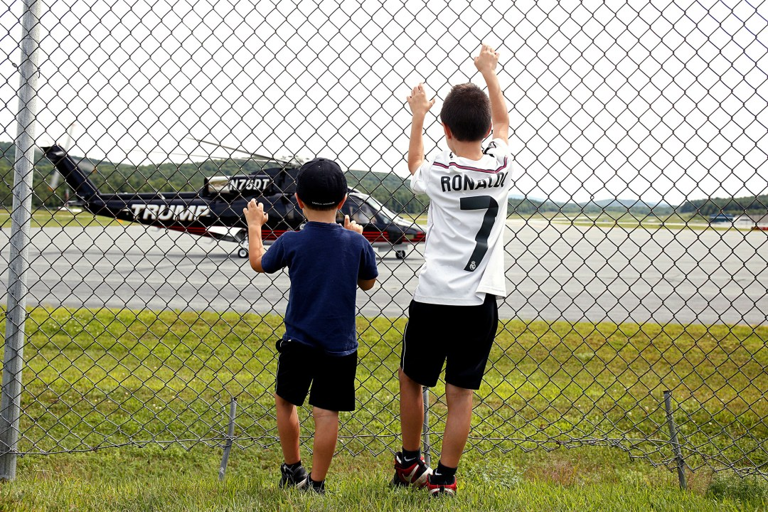 Cody McKinstry, 10, of East Thetford, Vt., and his brother Kaleb, 5, watch a helicopter with the Trump name written on the side take off from Lebanon Municipal Airport in West Lebanon, N.H., on Aug. 14, 2017.
