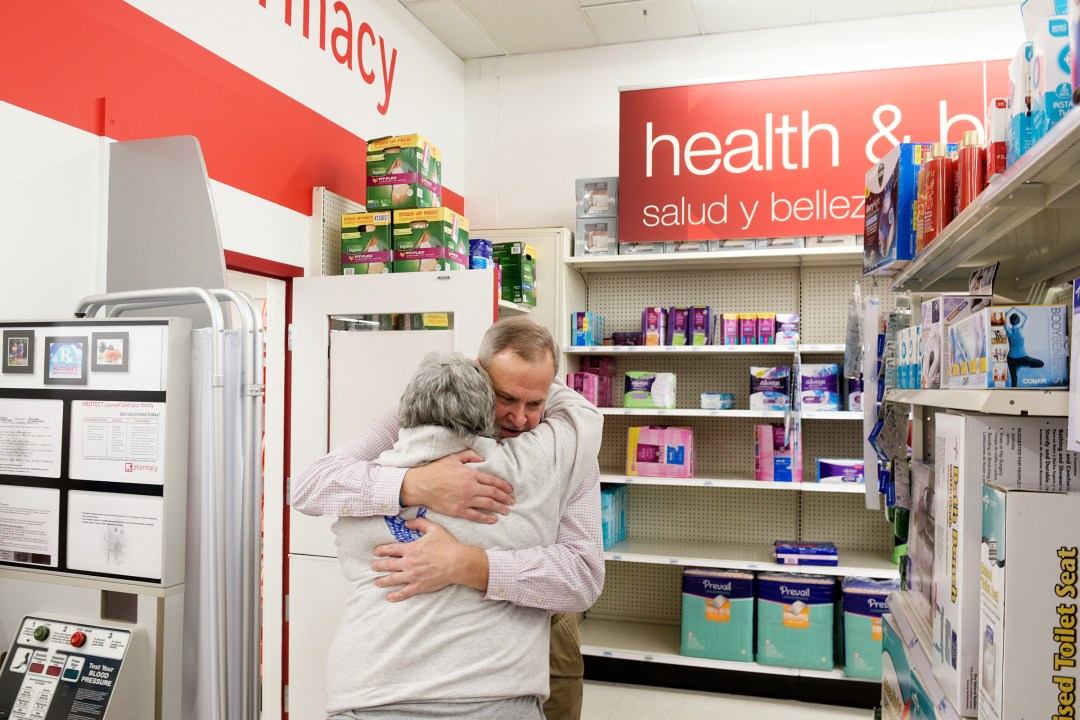 """Pharmacist Dave Ambrose, of Lebanon, gets a hug from customer Linda Nordman, of White River Junction, at K-Mart in West Lebanon, N.H., on Tuesday, December 5, 2017. It was Ambrose's last day serving customers as the pharmacy was set to close permanently at 4 p.m. Tuesday. """"I'm really kind of sad,"""" said Nordman, who said she will miss Ambrose and the pharmacy staff. """"They all take an interest in what's going on in your life."""" (Valley News - James M. Patterson) Copyright Valley News. May not be reprinted or used online without permission. Send requests to permission@vnews.com."""