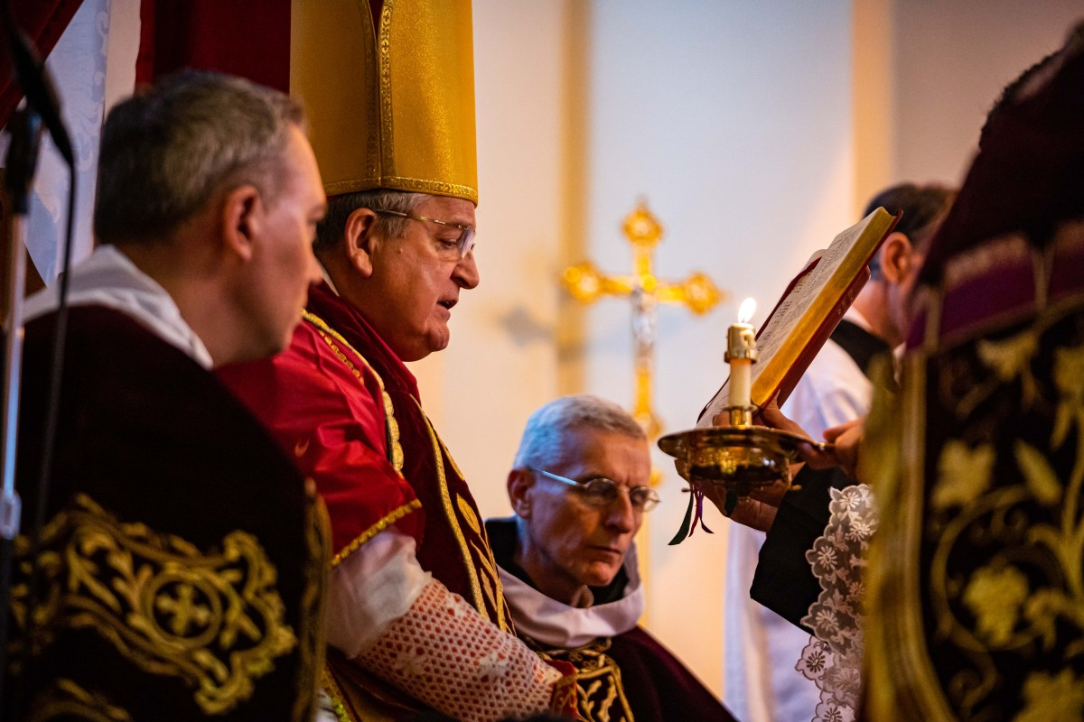 Cardinal Burke celebrates Pontifical High Mass, gold crucifix visible in background