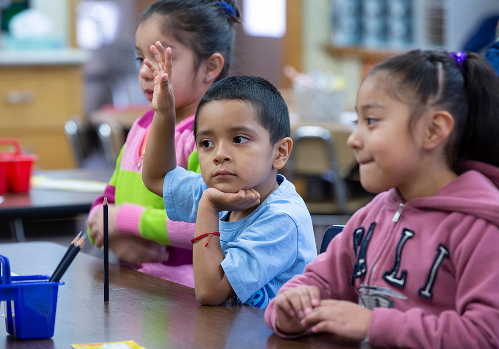 kid raising hand at summer learning program