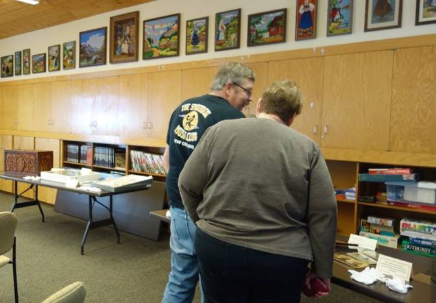 Community members looking at objects.