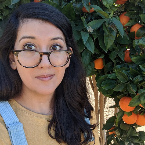 Photo of Laura Villareal with dark long hair parted to the side, wearing large tortoise shell rimmed glasses on the bridge of her nose, wearing a pale yellow shirt and light blue overalls. She is smiling at the camera and standing next to an orange fruit tree with green leaves.