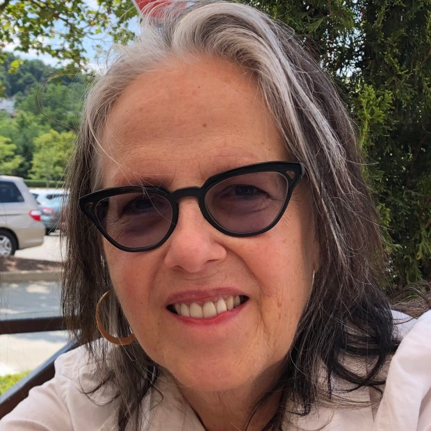 Judith Vollmer pictured with gray hair streaked elegantly with white, wearing a pair of cat-eyed black glasses and a white shirt, looking at the camera and smiling.