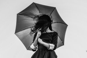 a lady holding an umbrella, her hair blowing in front of her face