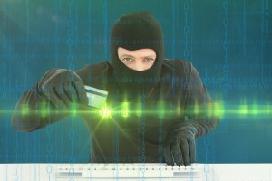 hacker with glowing green credit card - Companies of All Types Face Cyber Attacks That Could Put Your Data at Risk