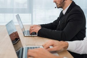 people working on laptop with headsets - Stopping Threats Before They Happen: 4 Ways Cisco Umbrella Protects Your Business
