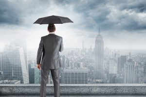 businessman using an umbrella and overlooking city - At V2 Systems, We Use Cisco Umbrella. You Should, Too.