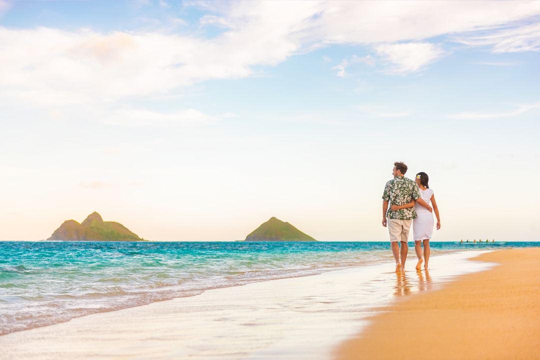 Hawaii beach vacation couple walking at sunset