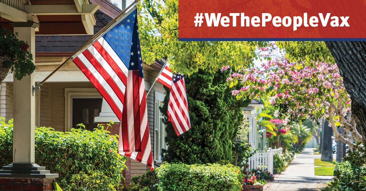 row of houses with American flags and #wethepeoplevax