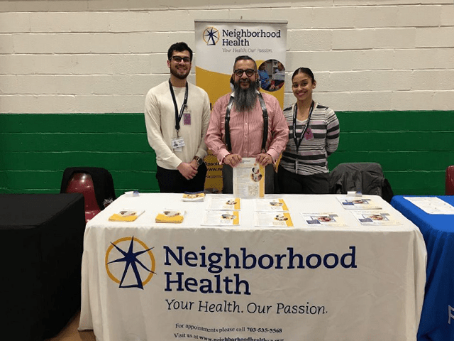 Neighborhood Health Booth with 3 people standing by the table