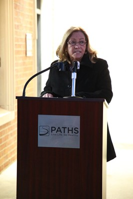 CEO Mendenhall at a podium speaking into a microphone