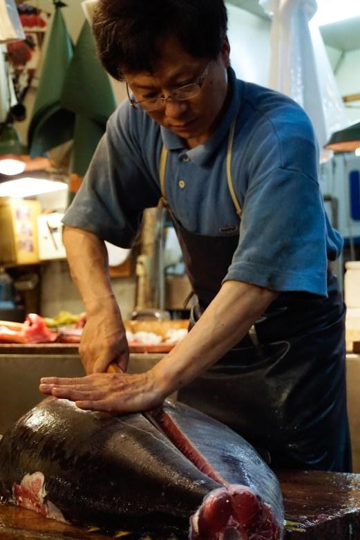 Carefully preparing a whole tuna.