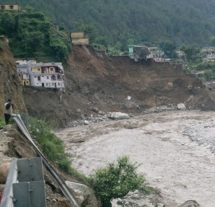 Houses hanging precariously on the river after water engulfed earthe beneath them,