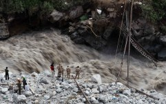 Water gushes down a river as Indian paramilitary soldiers and volunteers stand near a makeshift bridge after it was damaged hampering to evacuate the stranded pilgrims in Govindghat.