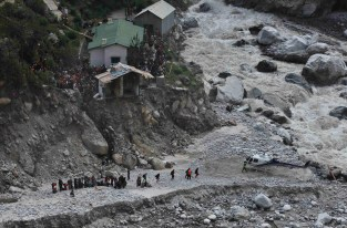 Stranded Indian pilgrims walk towards a waiting helicopter after they were evacuated in Govindghat