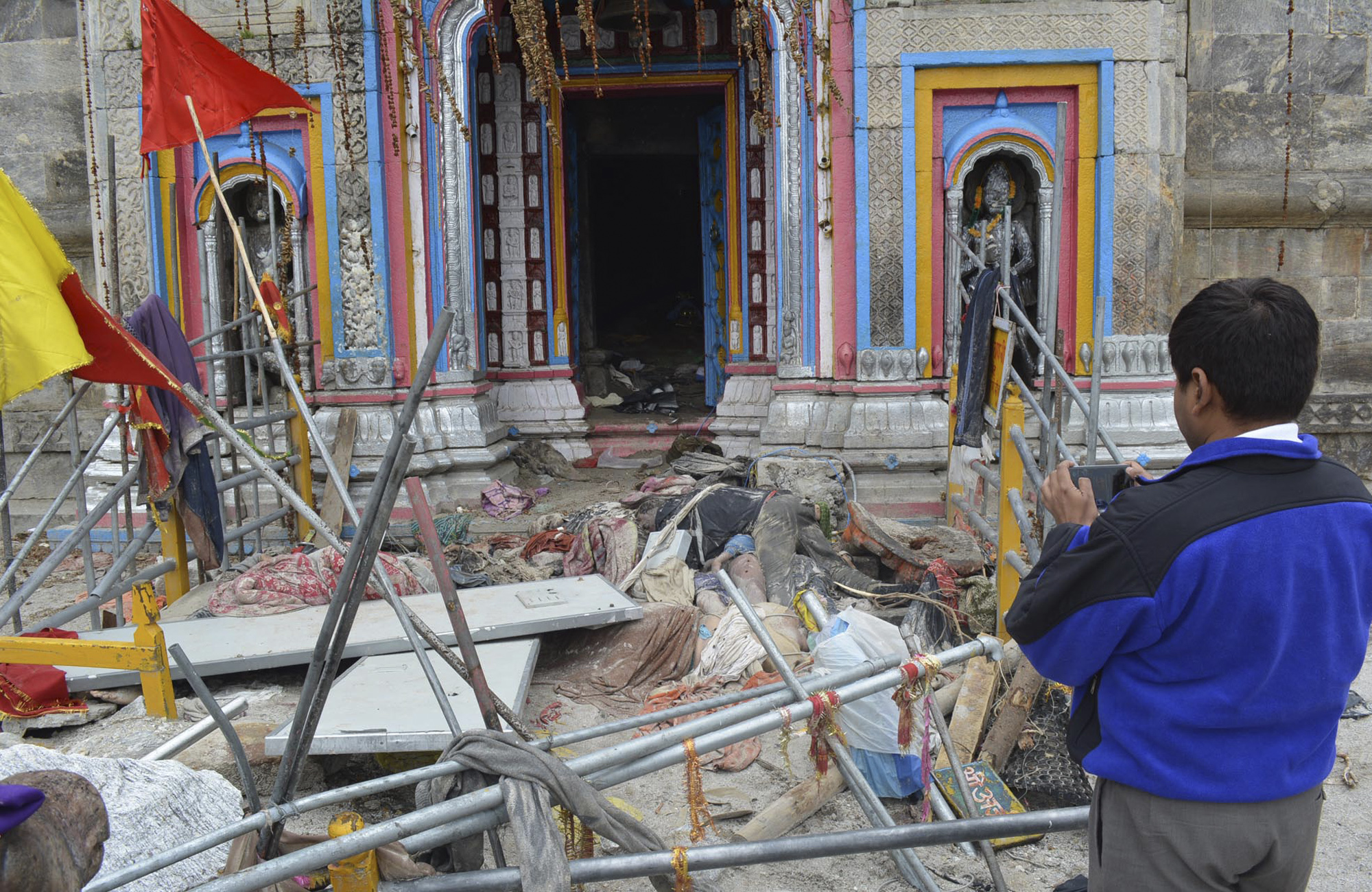 In this Thursday June 20, 2013, photo, a visitor takes photographs as bodies of pilgrims are seen lying in from of the Kedarnath shrine, one of the holiest of Hindu temples dedicated to Lord Shiva at Kedarnath, in the northern Indian state of Uttrakhand.
