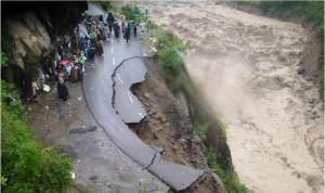 In this handout photograph released by The Indian Army on June 18, 2013, Indian security personnel supervise residents and travellers as they stand on the remains of a flood damaged road alongside the River Alaknanda in Chamoli district in the northern Indian state of Uttarakhand on June 18, 2013.  Torrential rains and flash floods washed away homes and roads in north India, leaving at least feared 60 people dead and thousands stranded, as the annual monsoon hit the country earlier than normal, officials said. Authorities called in military helicopters to try to rescue residents and pilgrims cut off by rising rivers and landslides triggered by more than three days of rain in the Himalayan state of Uttarakhand, officials said.