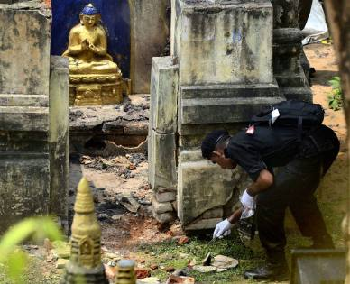 An NSG expert collecting samples at Mahabodhi Mahavihara in Bodhgaya on Monday, a day after serial blasts in the temple