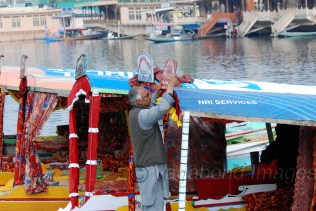 A shikara owner placing the signboard of his shikara perfectly