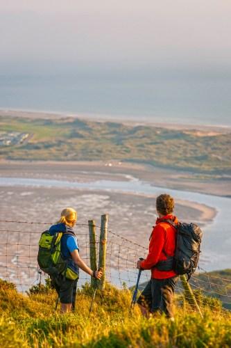 Couple walking on Wales Coast Path overlooking Dovey estuary Near Aberdovey