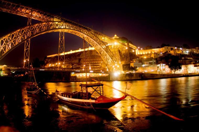 Vista nocturna desde la Ribeira del puente Don Luis I sobre el río Duero, en Oporto