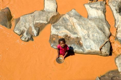Niña buscando oro en el río