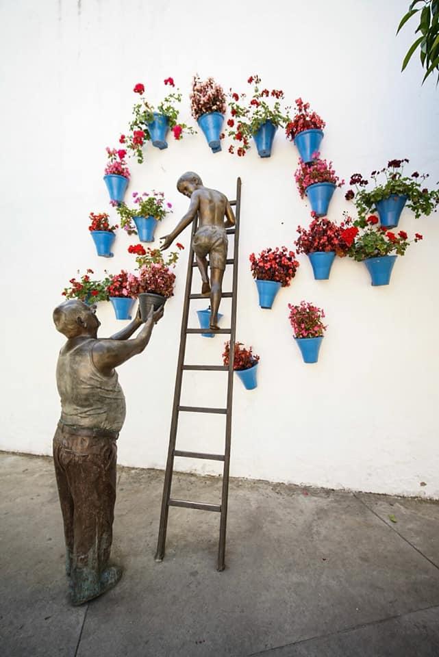 Estatua de un hombre y un niño colocando macetas de flores en una pared en las calles de Córdoba