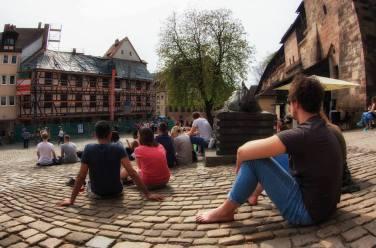 Con buen tiempo la gente se sienta en el suelo empedrado de la plaza Tiergärtnertor, Nuremberg