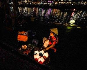 Niña vendiendo velas por la noche en Hoi An