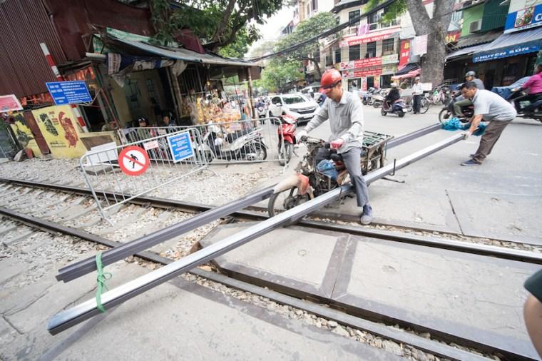 Transportando vías de tren en una moto por las calles de Hanoi