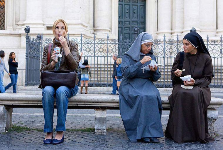 """Poster de la película """"Come, Reza, Ama"""" en la Plaza Navona de Roma"""