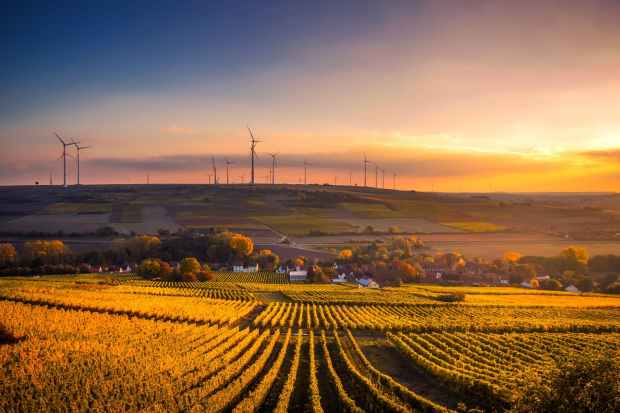 Scenic view of agricultural field with wind power farm against sky during sunset