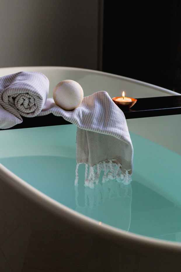 relaxing bathtub indoors with a candle flickering, bath bomb, and blanket draping on a wooden stand