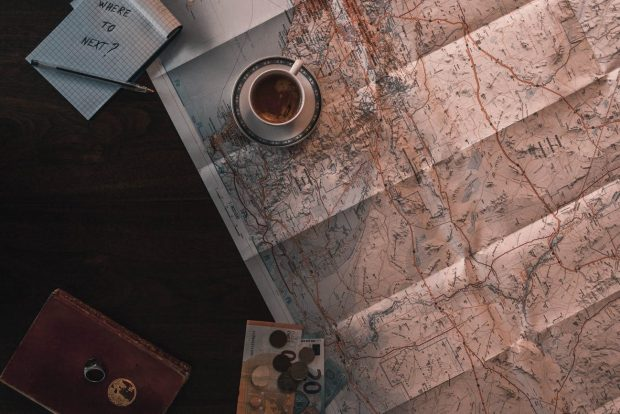 tea cup on a map with a notebook planning where to go next