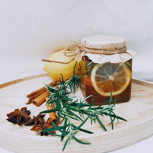 A photo of a reusable jar with a lemon, cinnamon sticks, a herb and a star-shaped spice. An example of reusing and homemade goods.
