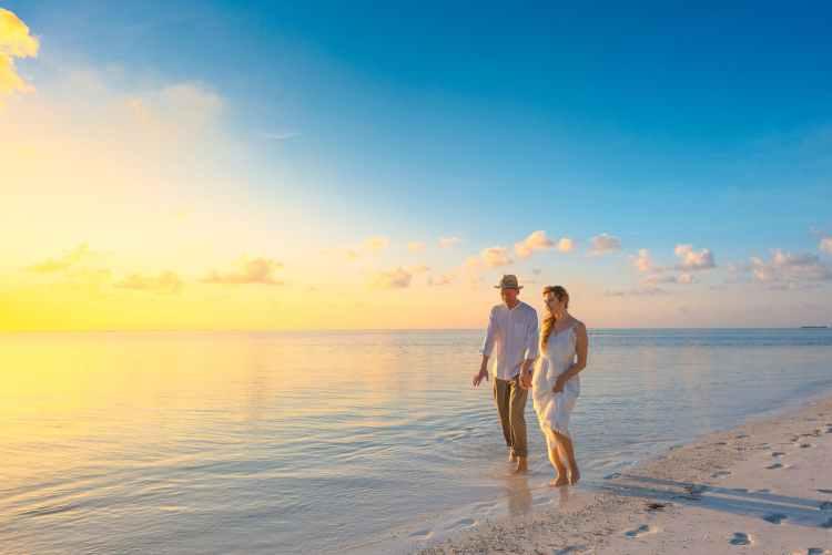 couple walking on seashore wearing white tops during sunset