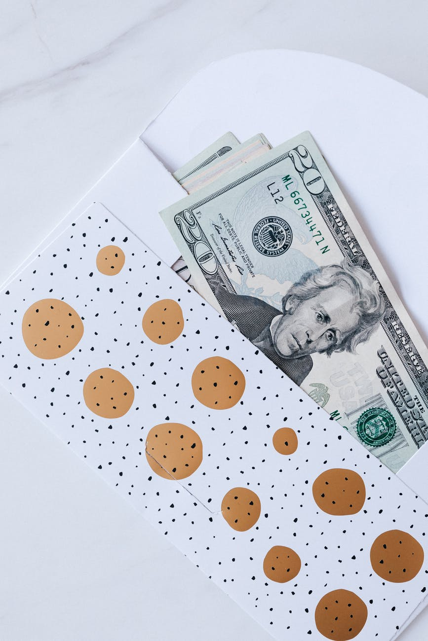 gift envelope with heap of greenbacks on marble table