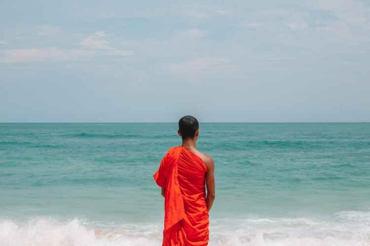 unrecognizable asian male monk in traditional orange robe on seashore