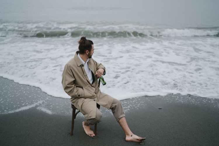 man sitting on stool at the seashore