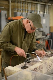 A mount-maker solders together pieces for one of the hundreds of custom-made object mounts used in The Story of Virginia.