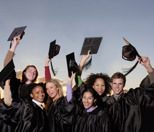 Graduates Lifting Mortarboards --- Image by © Royalty-Free/Corbis