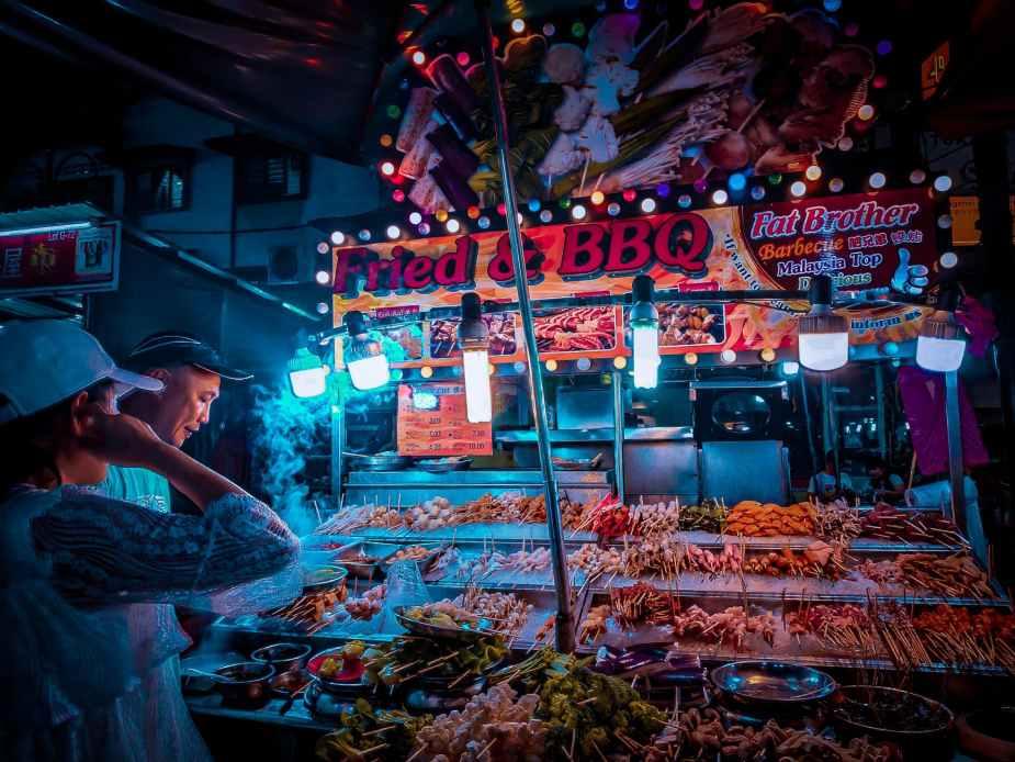customer choosing raw kebab in street stall at night