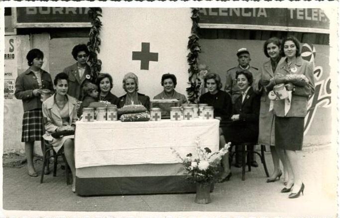 FOTOGRAFÍA DAMAS DE LA CRUZ ROJA. MESA PETITORIA. MILITAR DE CRUZ ROJA DETRÁS. VALENCIA 1960. Fuente: todocolección.net