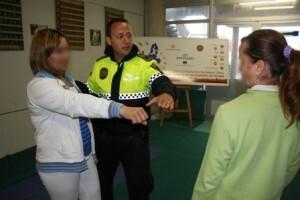 Un agente explica a dos mujeres como protegerse en caso de ataque/plv