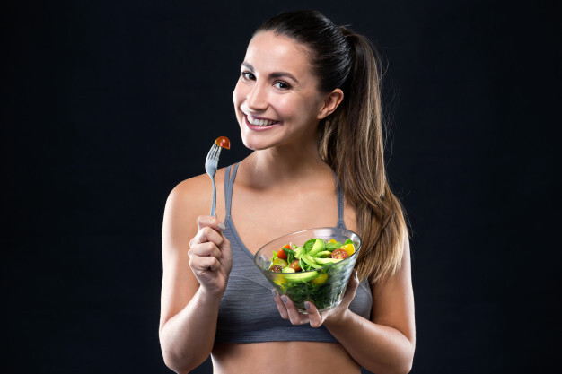 beautiful-young-woman-eating-salad-black-background_1301-7563