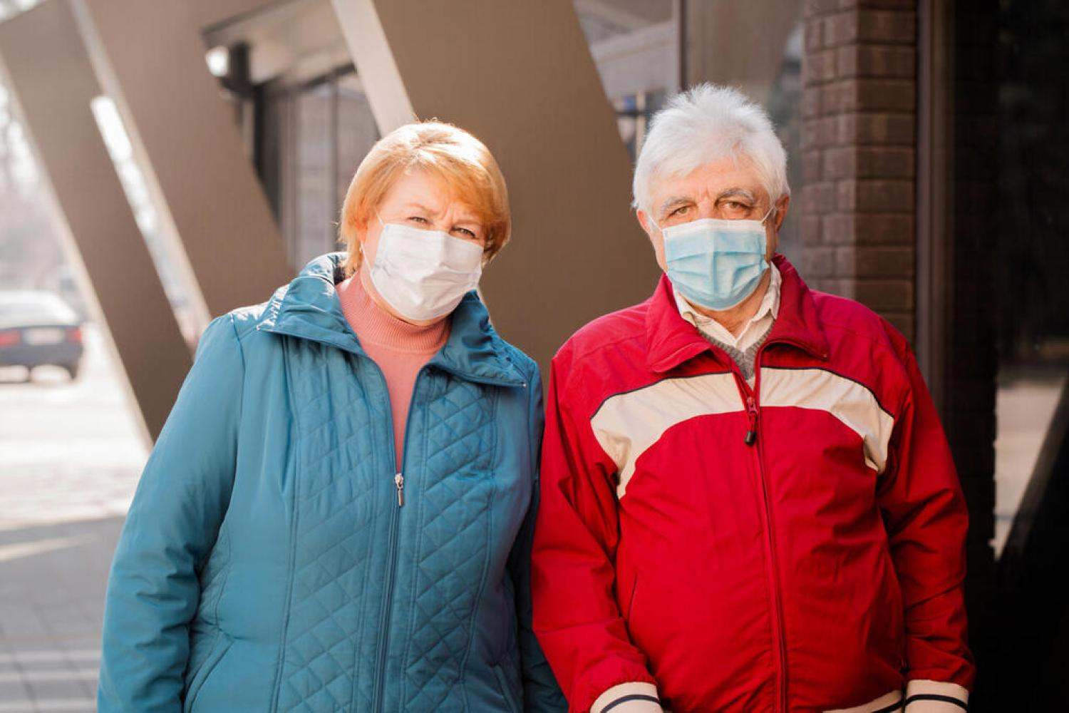 An elderly couple of people in protective masks. Coronavirus Protection Concept
