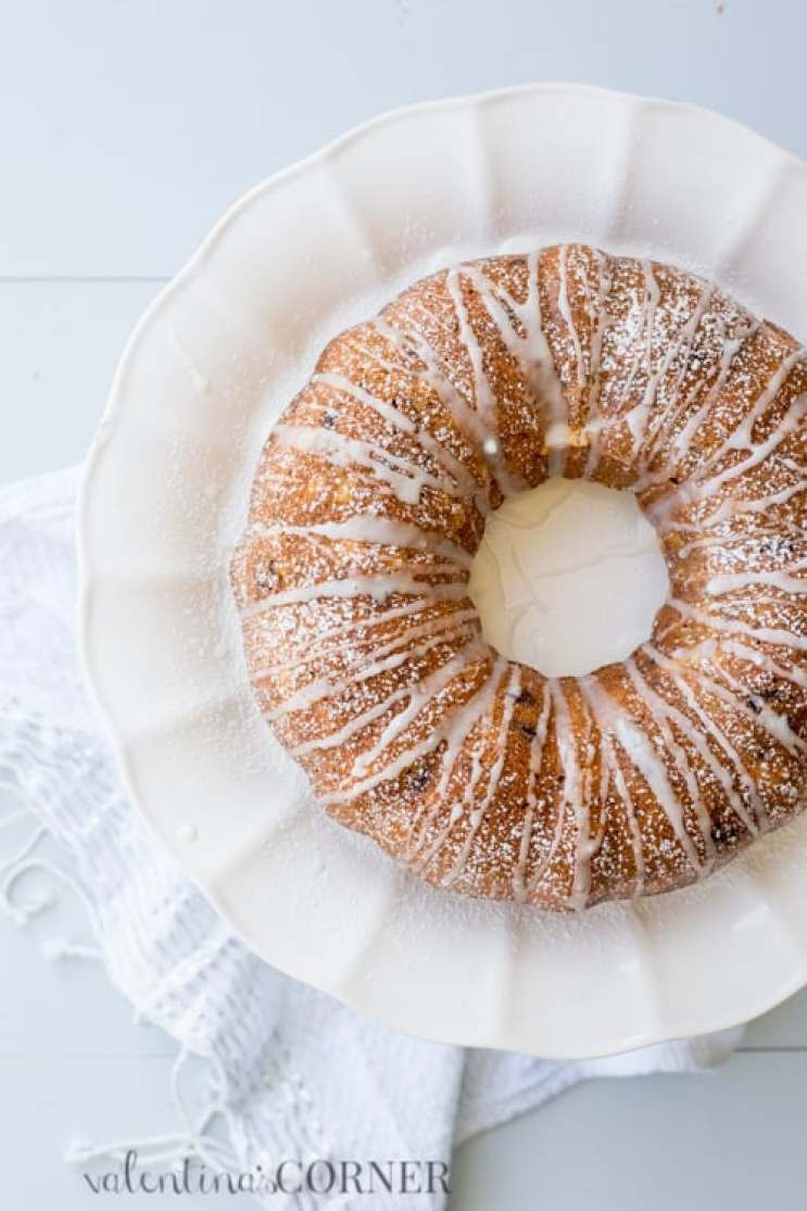 Banana bread bundt cake with cream cheese on a platter with sprinkled powdered sugar and icing drizzled.