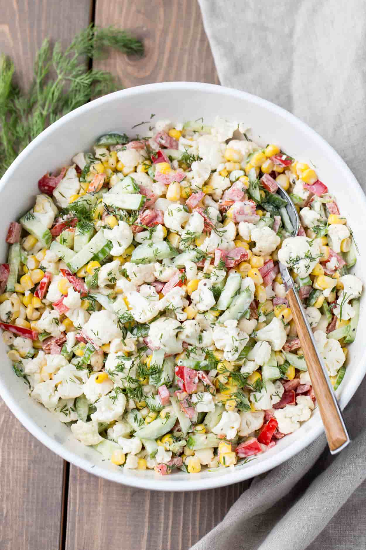 Corn salad with cucumbers in a bowl.